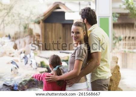 Happy family looking at penguins at the zoo - stock photo