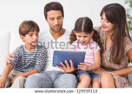 Happy family looking at tablet pc on the couch - stock photo