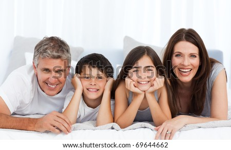 Happy family looking at the camera on their bed - stock photo