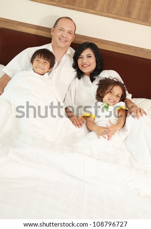 happy Family lying down in the bedroom - stock photo