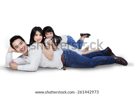 Happy family lying down on the floor while smiling at the camera, isolated over white background - stock photo