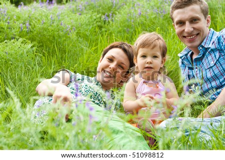 Happy family lying in the blooming meadow - stock photo