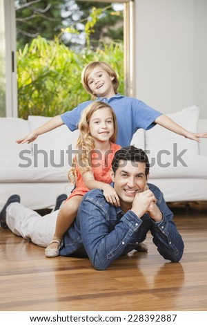 Happy family lying on floor in living room - stock photo