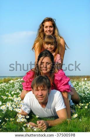 Happy family lying on grass - stock photo
