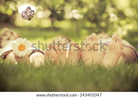 Happy family lying on green grass. Children having fun outdoors in spring park. Retro toned - stock photo