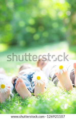 Happy family lying on green grass outdoors in spring park - stock photo