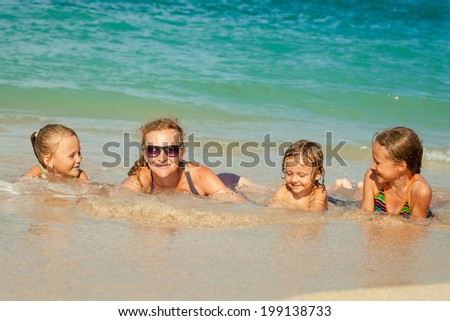 Happy family lying on the beach at the day time - stock photo