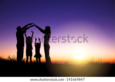 happy family making home sign on the hill with sunrise background - stock photo