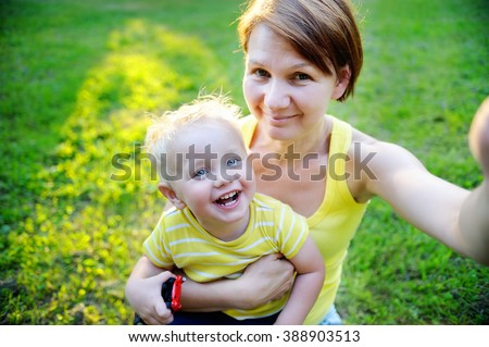 Happy family: middle age woman and her adorable toddler grandson at park making selfie - stock photo