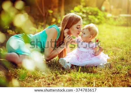 happy family. Mom and baby resting in a meadow in the summer outdoors in the park - stock photo