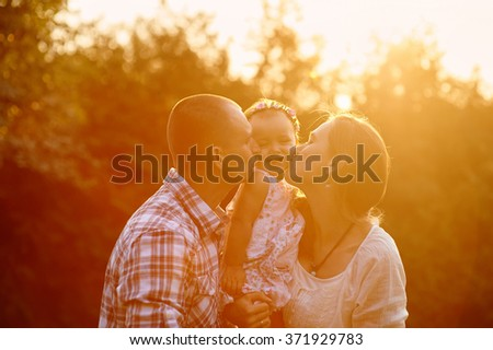 happy family Mom and Dad holding daughter in his arms and kiss her in the park. - stock photo