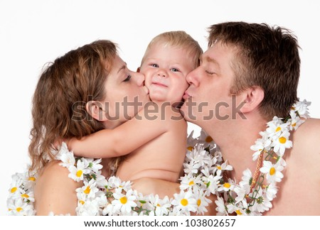 Happy family: mom and dad kiss a son - stock photo