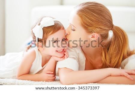 happy family. Mom kisses her little daughter child - stock photo