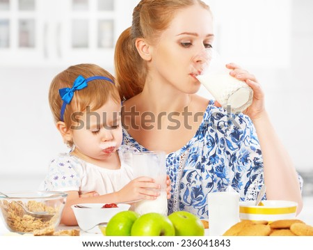 happy family mother and baby daughter  child girl at breakfast: biscuits with milk - stock photo