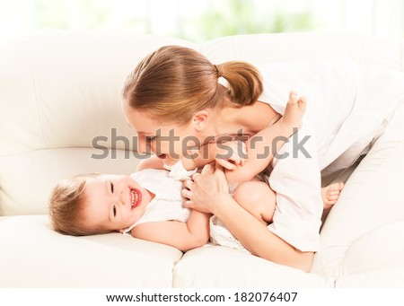 happy family. Mother and baby daughter plays at home on the sofa  - stock photo