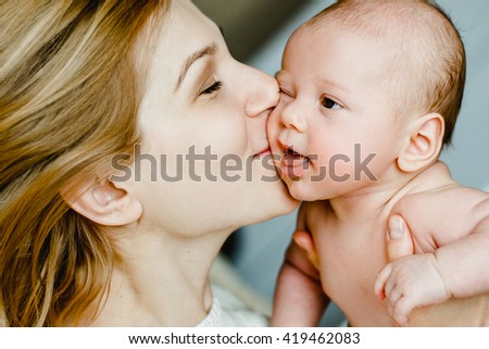 happy family mother and baby having fun playing, kissing laughing on the bed.  - stock photo