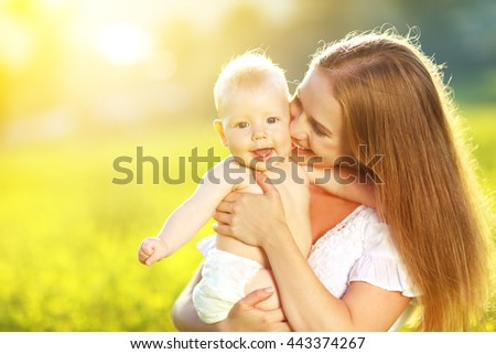 happy family mother and baby hugging and laughing in summer on the nature - stock photo