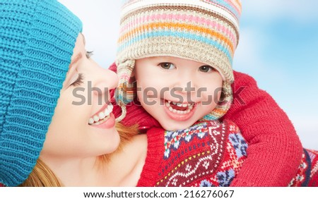 happy family mother and baby little daughter playing in winter in warm sweaters and hats - stock photo