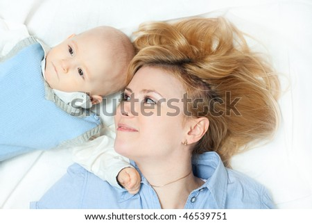 happy family: mother and baby lying down and smiling -  on white - stock photo