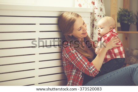 happy family mother and baby playing at home window - stock photo