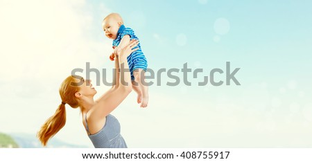 happy family mother and baby son playing and having fun in the summer by the sea on the beach - stock photo