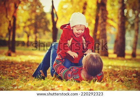 happy family: mother and child little daughter playing and laughing in the autumn on the nature walk outdoors - stock photo