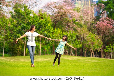Happy family mother and child little daughter running and playing at park - stock photo
