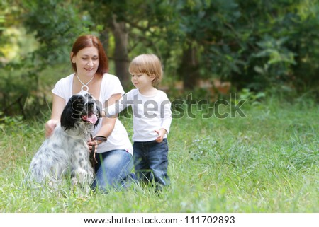 happy family - mother and child - playing with dog outdoors - stock photo