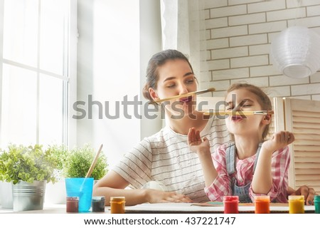 Happy family. Mother and daughter paint together and fooling around. - stock photo