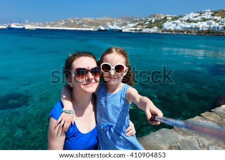 Happy family mother and her adorable little daughter on vacation taking selfie with a stick on Mykonos island, Greece - stock photo
