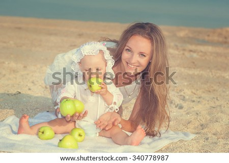 Happy family. Mother and her daughter having fun on the beach. With green apples. Positive human emotions, feelings. - stock photo