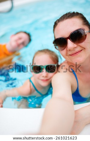 Happy family mother and her kids at outdoors swimming pool taking selfie on tropical vacation - stock photo