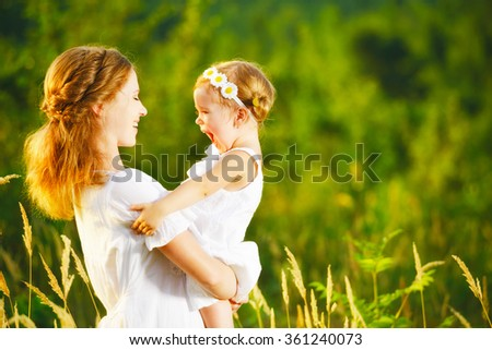 happy family, mother and little daughter girl child in the summer meadow  - stock photo