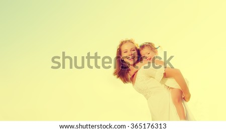 happy family, mother and little daughter girl child play and have fun in the summer  - stock photo