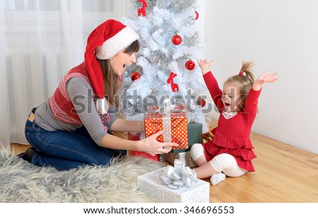 happy family mother and little daughter in front of christmas tree with presents and gifts for holidays - stock photo