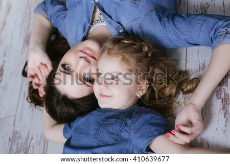 Happy family mother and little daughter lie on the floor dressed in jeans dress - stock photo