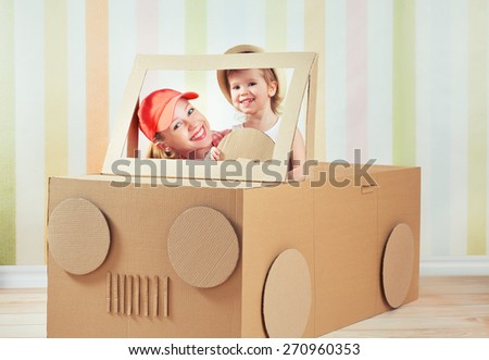 Happy family mother and little daughter ride on toy car made of cardboard on vacation - stock photo