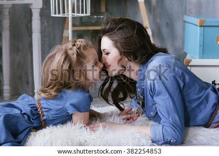 Happy family mother and little daughter rub against each other noses dressed in jeans dress - stock photo