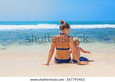 Happy family - mother and small baby son sit on sand beach and look at sea surf before swimming in clear water. Active parents and people outdoor activity on tropical summer vacations with child. - stock photo