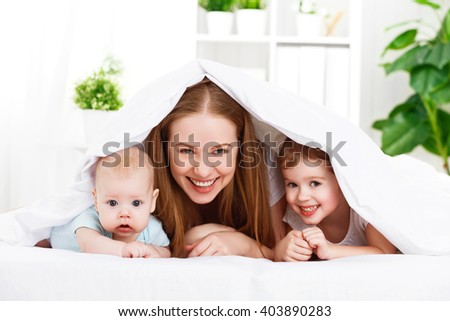 happy family mother and two children, son and daughter in bed playing  under  blanket - stock photo