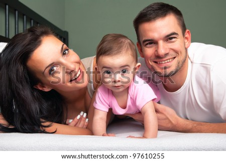 Happy family - mother, father and baby on the bed - stock photo