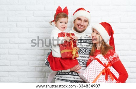 Happy family mother, father and child at Christmas blank brick wall - stock photo