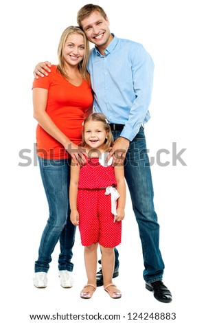 Happy family. Mother, father and cute daughter posing in trendy outfits - stock photo