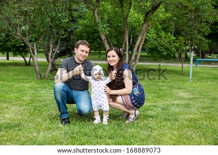 Happy family: mother, father and daughter baby playing in the park - stock photo