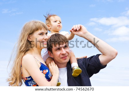 Happy family - mother, father and daughter. Blue skies on the background. - stock photo
