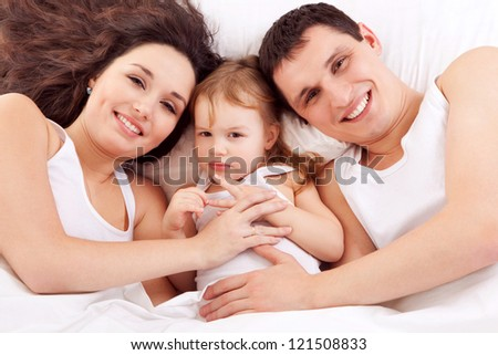 Happy family, mother, father and daughter resting on the white bed - stock photo