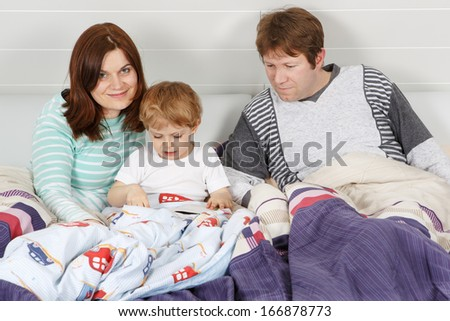 Happy family: Mother, father and little son reading book before going to bed - stock photo