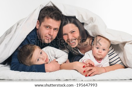 happy family, mother ,father and their baby and boy under the blanket on the bed. on white background - stock photo
