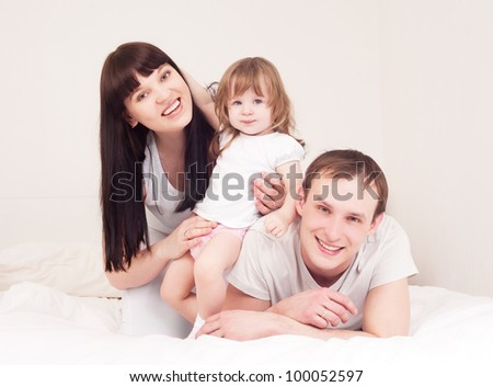 happy family; mother ,father and their baby in bed at home - stock photo
