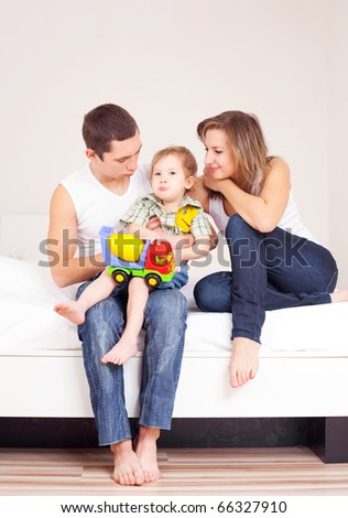 happy family, mother ,father and their baby on the bed at home - stock photo